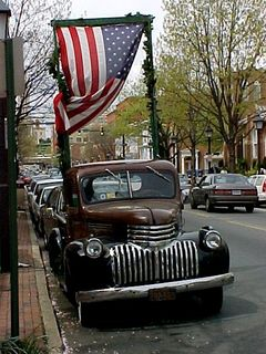 This is just the coolest car! It's a vintage truck for starters, then I love the way the owner has attached the frame on the back for holding the American flag on it...