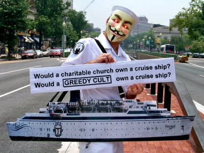 A man dressed in a nautical theme and wearing a cutout of the MV Freewinds holds a sign questioning why a church would own a cruise ship.