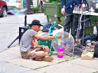 A man wearing a pirate outfit sits on the sidewalk blowing bubbles via an electric fan.