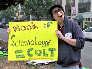 A man wearing a fake mustache and glasses holds a sign for motorists, indicating that they should honk their horn if they believe that the Church of Scientology is a cult.