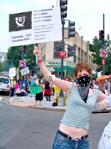A masked woman holds a sign identifying Anonymous, and questioning why a cult would need its own navy.