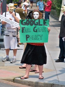 """A woman wearing a white mask holds a sign telling passers-by to search """"Fair Game Policy"""" on Google."""