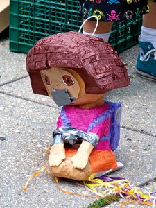 A Dora the Explorer piñata sits bound and gagged on the pavement, prior to being smashed open.