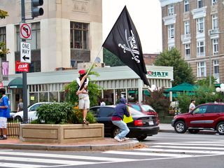 A man holds a large pirate flag in the air in the median of Connecticut Avenue NW.
