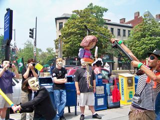A person wearing a sportcoat and Guy Fawkes mask winds up to take a swing at a Dora the Explorer piñata.