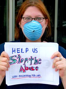 A woman wearing a dust mask holds up a handwritten sign giving the address of Ex-Scientology Kids.