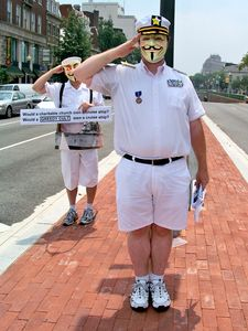 Two men dressed in nautical attire give a salute in the median of Connecticut Avenue NW.