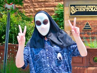 A man wearing an alien mask poses in front of the Founding Church of Scientology.