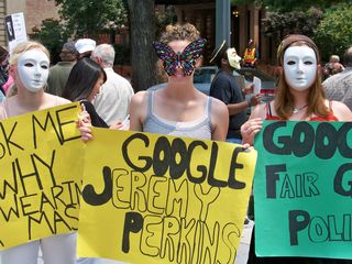 Three women wearing masks hold their signs at the intersection of Connecticut Avenue and 20th and R Streets NW.