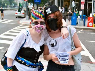 Two women take a moment away from passing out flyers to pose for a photograph.