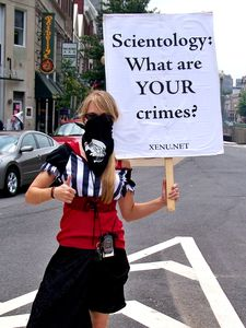 A woman gives the thumbs-up while holding a sign asking the Church of Scientology what its crimes are.