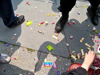 Some of the candy from the Dora the Explorer piñata lays on the sidewalk as people come around to collect it.