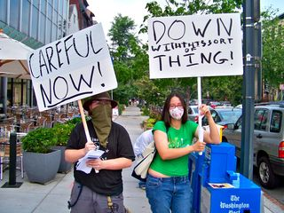 Two masked individuals hold signs critical of the Church of Scientology.