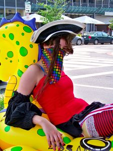 A masked woman poses on an inflatable tube in the median of Connecticut Avenue NW.