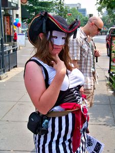 A masked woman fully decked out in pirate style poses for the camera.