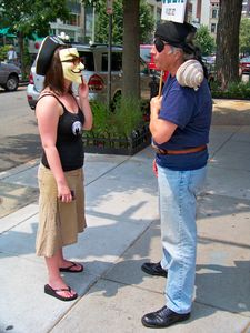A woman in a Guy Fawkes mask carries on a conversation with Arnie Lerma on the sidewalk in front of the Founding Org.