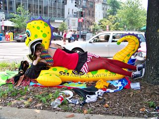 A masked woman strikes a pose on an inflatable tube in the median of Connecticut Avenue NW.