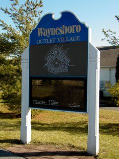 """These welcome signs also illustrated the Outlet Village's identity crisis. Some signage, like the tall sign and some of the welcome signs, used the older """"Waynesboro Outlet Village"""" logo. Others used a newer """"Waynesboro Village"""" logo. The newer name, however, never caught on with the local community."""