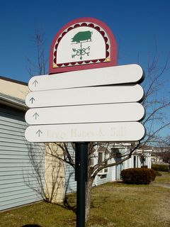 """These signs helped visitors navigate the Outlet Village, by indicating which stores were right around the corner. In the facility's heyday, all of these signs were six-tiered. Over the years, some signs were shortened. This was also the only place where """"labelscar"""" (markings left over after signs were removed) could be found, indicating former tenants."""