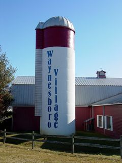 """The silo originally was painted to advertise the Gitano outlet. After the Gitano outlet left, the silo was repainted to say """"Waynesboro Village"""" in a similar style as the old paintwork. While the Artisans Center occupied the building, the red band said """"Artisans Center"""" in white letters. This was painted out when the Artisans Center relocated to another building in the facility."""