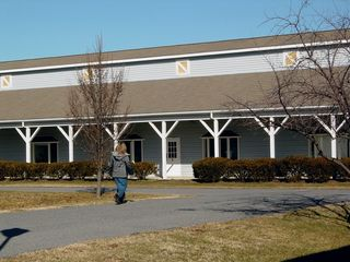 """Building 5 was somewhat unique in its appearance, as it was taller than most of the other buildings, and lacked a cupola. This building once housed a store called """"Petal Pushers"""" in one of its three spaces. At the time of the facility's closing, Building 5 housed offices."""