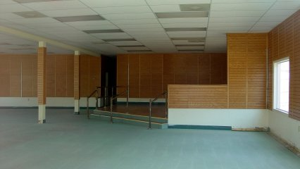 Inside Building 10, one finds a store with wood paneling on the walls, a raised area to the rear, and a green carpet. The name of the former tenant is unknown.