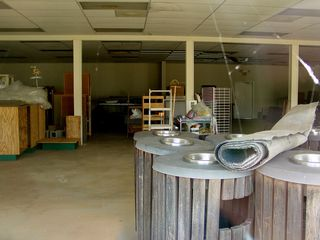 In another building, various equipment sits in storage. The combination trash can and ashtray units were formerly located outside all along the walkway, and the brown boxes with the green bases are believed to have come from the former Bass Shoes space.