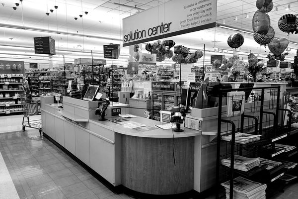 Plexiglass screens, ostensibly to prevent the transmission of COVID-19 between patrons and store employees, hung from the ceiling in front of the customer service counter at a Giant Food store in Montgomery Village, Maryland.