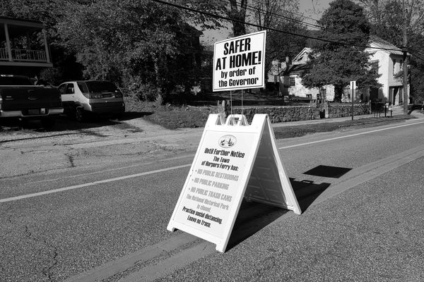 A-frame sign in the middle of Washington Street in Harpers Ferry, West Virginia advising potential visitors to the historical park that there are currently no public restroom facilities, no public parking facilities, and no trash cans.