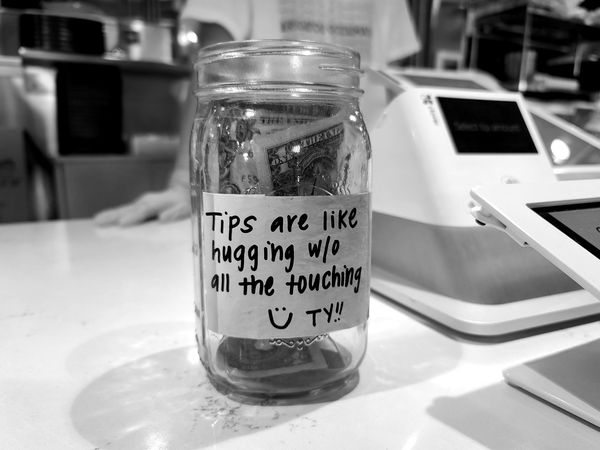 Sign on a tip jar at Pike Kitchen, an Asian food hall in Rockville, Maryland, characterizing tips as contactless hugs.