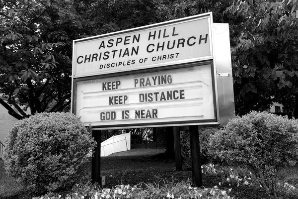 Sign at Aspen Hill Christian Church advising passers-by to keep praying and to keep their distance.