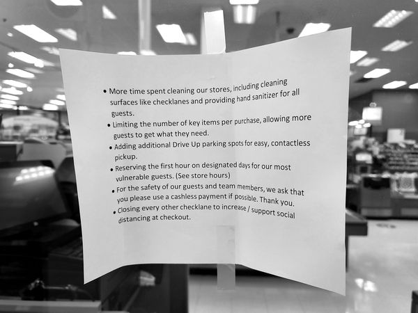 Sign on a plexiglass partition listing all of the various measures that Target has taken towards efforts to limit the spread of COVID-19, including additional cleaning, purchase limits, senior hours, and closure of certain checkout lanes.