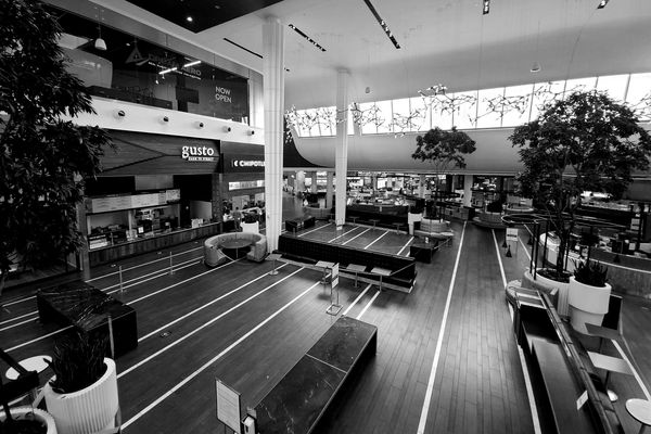 Food court at Montgomery Mall, a shopping mall in Bethesda, Maryland. Nearly every portable piece of furniture has been removed, and any built-in tables and seats have been blocked off.