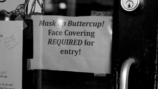 """Sign reading, """"Mask up Buttercup!"""" on the front door of Twisted Branch Tea Bazaar, a restaurant in downtown Charlottesville, Virginia, in an attempt to be cute while conveying masking requirements."""
