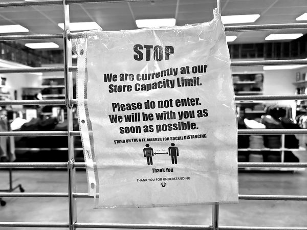 Sign on the gate at the True Religion store at the Arundel Mills shopping mall in Hanover, Maryland, preventing customers from coming in as a method of enforcing capacity limitations, ostensibly to prevent the spread of COVID-19.
