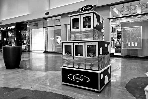 Coin-operated candy machines, wrapped in plastic to prevent usage, presumably in an attempt to prevent the spread of COVID-19.