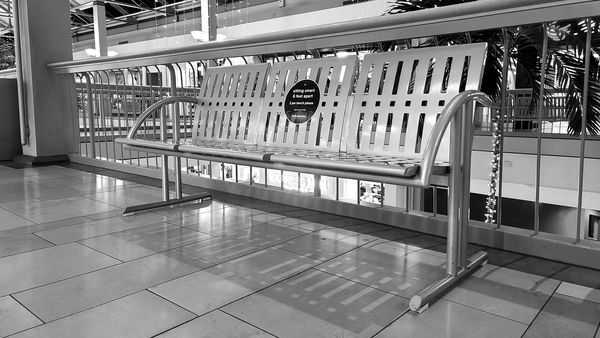 Social distancing marker on a bench at White Marsh Mall in Nottingham, Maryland, indicating that only two people are allowed to sit on the bench at one time.