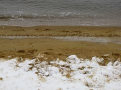The beach is covered in snow until a few feet from the water.