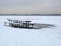A picnic table is covered in snow, with a pool of water nearby.