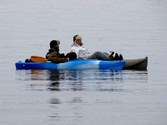 Two men float in small boats out in the bay.