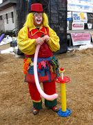 A man dressed in a clown costume makes balloon animals.