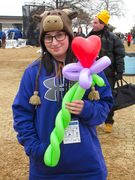 """A woman holds up a """"balloon animal"""" for the camera."""