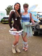 Two women dressed festively, the woman on the right complete with wings.
