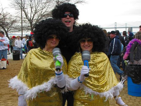 Three people dress up in gold outfits and Afro wigs.