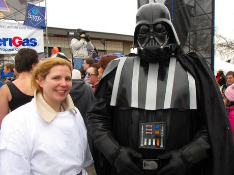A woman dresses as Princess Leia, and a man dresses as Darth Vader, both characters from Star Wars.