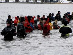 Support personnel in drysuits are in the water in preparation for participants' taking the plunge.
