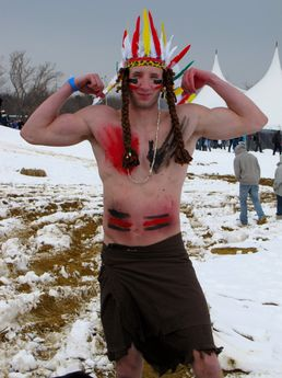 A man shows off his muscles for the camera while dressed in stereotypical Native American markings.
