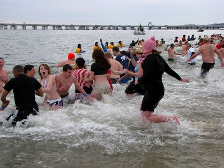 The first plunge is underway, as people run into the ice-cold waters of the Chesapeake Bay.