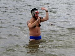 A man wearing a speedo and a winter hat takes a photo from the water.