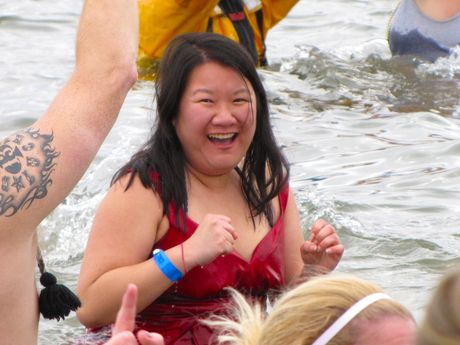 A woman in a red dress is all smiles as she stands in the water.